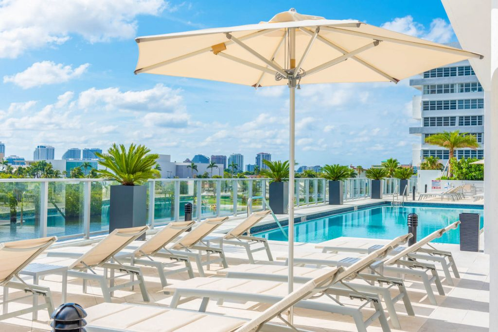 Riva Riverfront Pool. Modern outdoor furniture with umbrella next to pool